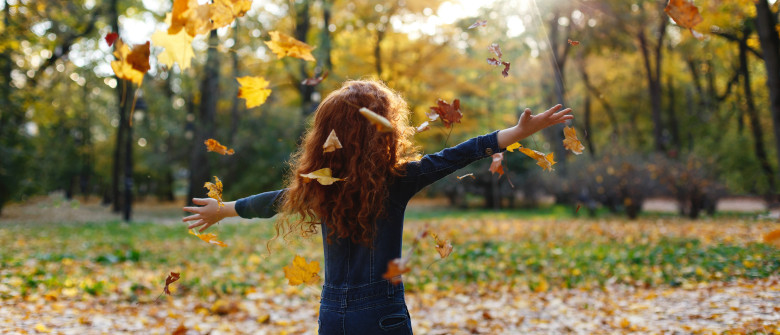 Autumn vibes, child portrait. Charming and red hair little girl looks happy walking and playing on the fallen leaves in autumn park full of evening sunshine